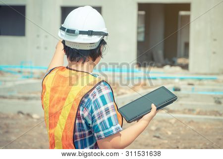 Asian Women Engineering Holds A Tablet For Use In The Inspection Of Construction Sites For Accuracy