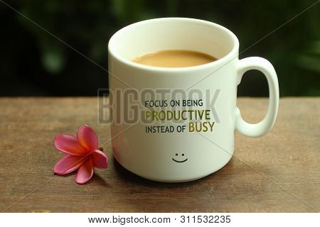 Morning Coffee Concept. Work Inspirational Quote On A Mug - Focus On Being Productive Instead Of Bus