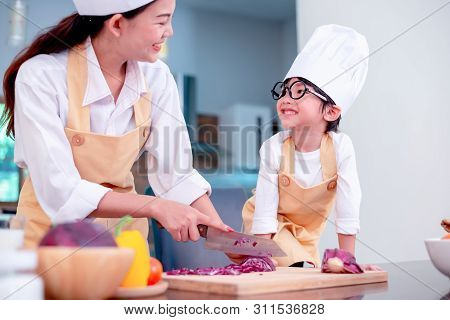 Happy Family In The Kitchen. Mom Teaching Son For Cook Healthy Food In Summer Holiday.