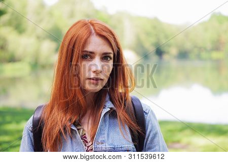 Authentic Young Woman Wearing Denim Jacket And Backpack Outdoors On A Hike - Real Person Standing By