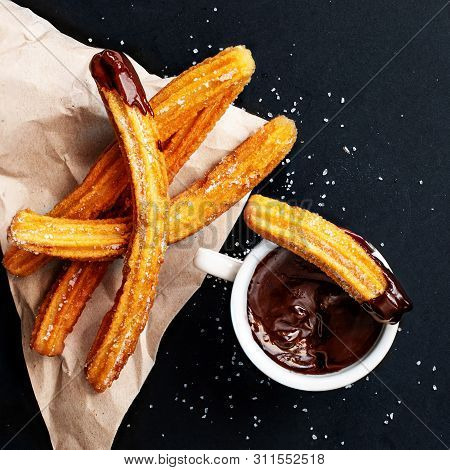 Churros With Sugar Dipped In Chocolate Sauce On A Black Background. Churro Sticks. Fried Dough Pastr