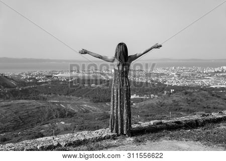 A Girl With Open Arms Stands On The Edge Of A Cliff
