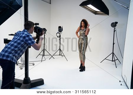 Photographer Working With Model On Fashion Shoot In Studio