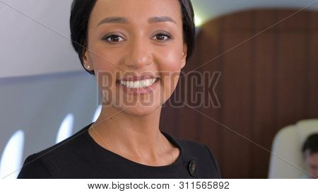 Stewardess portrait in private jet. Female biracial flight attendant smiling inside of business airplane cabin with passengers on background.