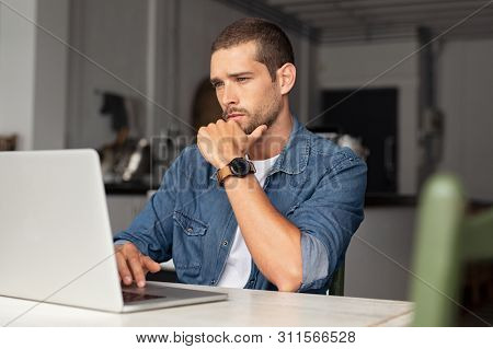 Serious young man working on laptop at home. Focused entrepreneur working on computer sitting at table. Thoughtful worried guy reading important articles and working on computer.