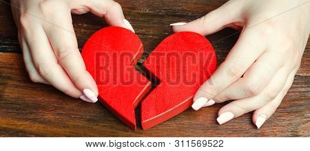 A Woman Collects A Broken Heart In His Hands. Concept Of Love And Relationships. Family Psychotherap