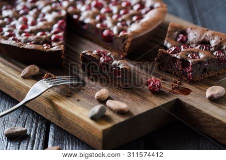 Yummy Chocolate Dessert. Homemade Brownies With Cherries And Cocoa Beans On Oak Board Low Angle View