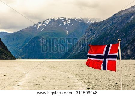 Norwegian National Flag Waving In The Wind In Sogne Fjord With Mountains In The Background, Aurlan,