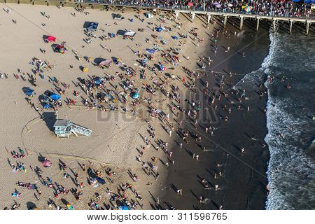 Santa Monica, California, USA - August 6, 2016:  Aerial view of summer crowds at popular Santa Monica beach and pier near Los Angeles.