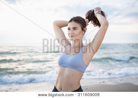 Pretty Brunette Woman Fixes Her Hair After Workout At The Sea Shore At Sunrise. Model Listening To T