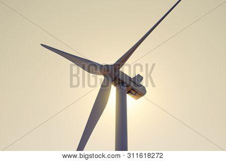 Wind Generator Turbine in Bright Sun Light on the Evening Sky Bacground. Green Renewable Energy Concept.