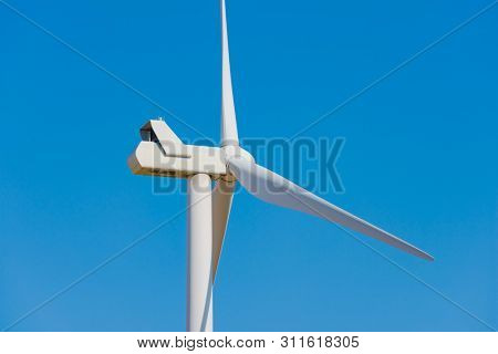 Wind Generator Turbine on the Clear Blue Sky Bacground. Green Renewable Energy Concept.