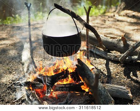 Cooking On A Campfire In Nature.cooking On A Campfire In The Siberian Forest.