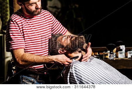 Barber Shaving A Bearded Man In A Barber Shop. Bearded Male Sitting In An Armchair In A Barber Shop