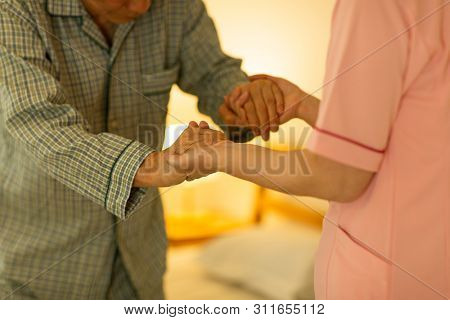 Senior man being cared by a female caregiver