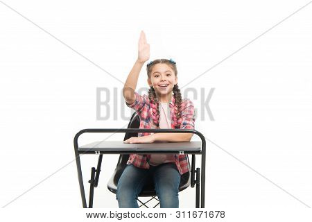 She Learnt The Lesson. Cute School Child With Raised Hand Sitting At School Desk. Little Schoolgirl