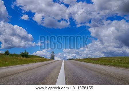 Low Angle View Of A Tarred Road Receding Into The Distance In Open Countryside Under A Cloudy Blue S