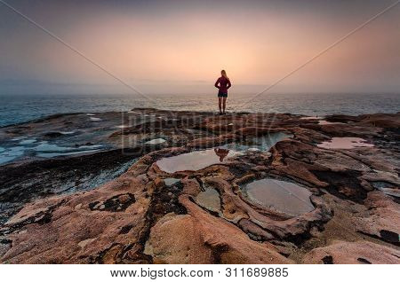 Woman Gazing Out To Sea With Foggy Coastal Sunrise And Foreground Puddles In Weathered Sandstone