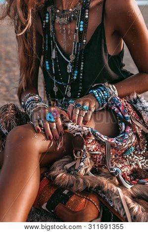 Close Up Of Young Boho Style Woman Sitting On Sand On The Beach At Sunset