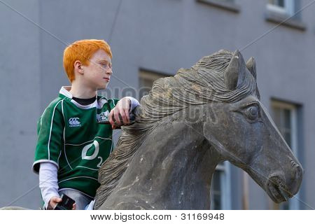 LIMERICK, IRELAND - MARCH 17: Unidentified boy on stone horse participates in a parade for St. Patrick's Day. It's a traditional Irish holiday celebration. March 17, 2012 in Limerick, Ireland.