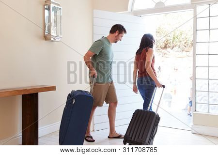 Mid adult white couple at their front door leaving home with luggage to go on vacation, full length