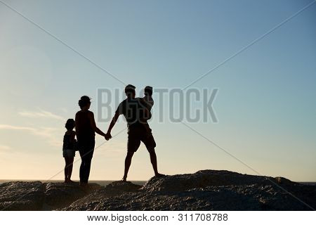 Mid adult parents and two pre-teen children standing on beach admiring view, full length, silhouette