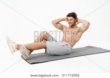 Attractive smiling young shirtless sportsman working out on a fitness mat isolated over white background