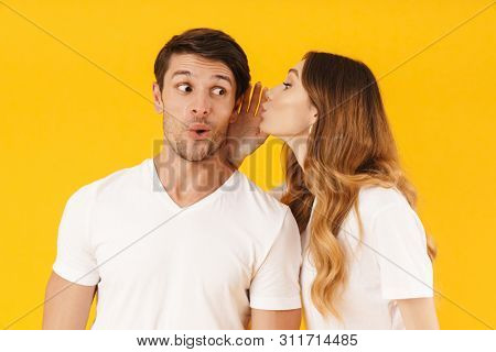 Portrait of joyful woman whispering secret or interesting gossip to excited man in his ear isolated over yellow background