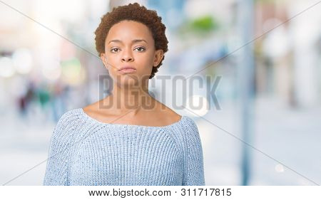 Young beautiful african american woman wearing a sweater over isolated background Relaxed with serious expression on face. Simple and natural looking at the camera.