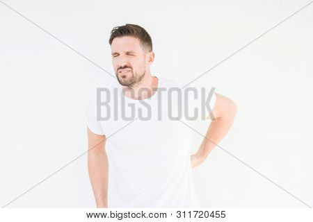 Young handsome man wearing casual white t-shirt over isolated background Suffering of backache, touching back with hand, muscular pain