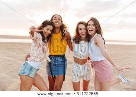 Photo of young happy smiling cheery women girls friends walking outdoors at the beach.