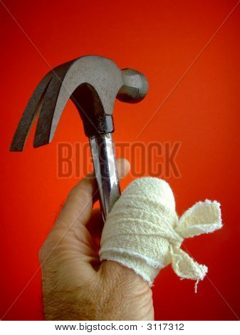 Close-up of a man's hand with the thumb wrapped in a huge bandage and also holding a hammer that could have done the damage. poster