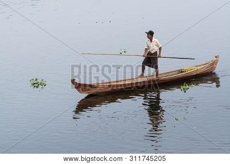 Nyaungshwe, Myanmar - April 2019: Burmese Man Leg Rowing In A Wooden Boat