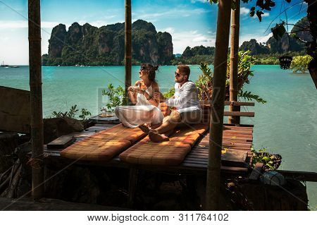 Happy Couple On An Island Off The Coast.  Young Couple Near  The Sea. Couple Travels Around The Worl