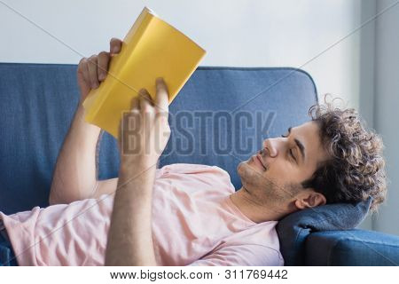 Man Relaxed And Reading A Book On Sofa