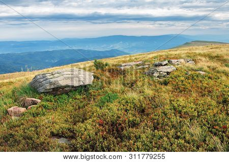 Grassy Meadow With Boulder On Top Of A Hill. Beautiful Summer Landscape In Mountains. Gloomy Weather