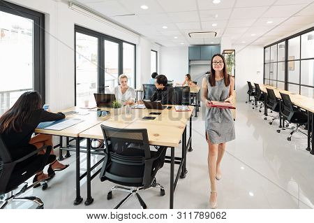 Young Asian Businesswoman Or Secretary With Folders Walking Along The Office Corridor With Other Bus