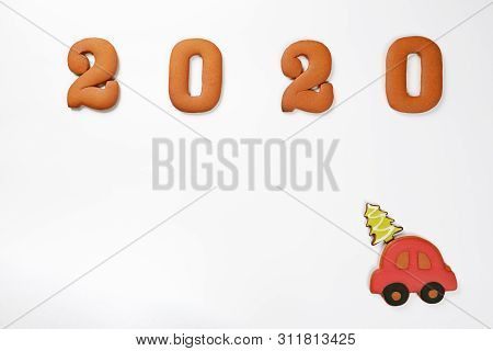 The hand-made eatable gingerbread 2020 inscription and gingerbread car with New Year tree on white background poster