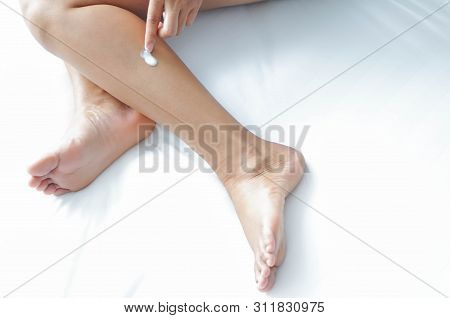 Woman Hand Applying Cream Or Lotion On Leg Lying On White Bed, Selective Focus