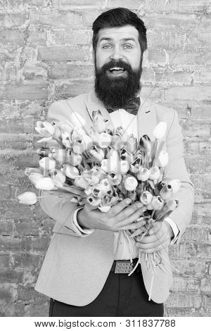 Romantic gift. Macho getting ready romantic date. Waiting for darling. Tulips for sweetheart. Man well groomed wear tuxedo bow tie hold flowers bouquet. Invite her dating. Romantic man with flowers. poster