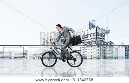 Man wearing business suit riding bicycle on penthouse balcony. Young cyclist with suitcase on background of business district. Terrace with modern downtown view. Time management and business activity poster
