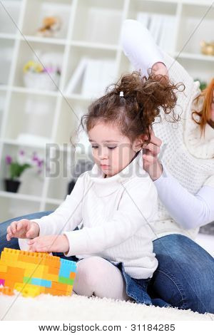 Mother  making hairstyle her  daughters