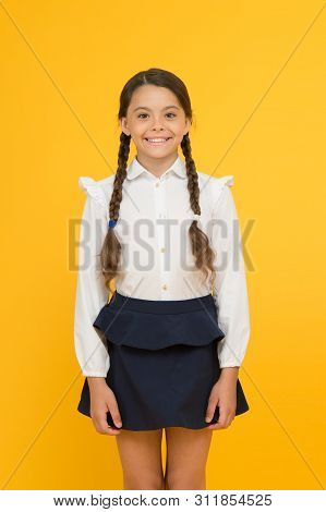 Smart Cutie. Cute Little Girl Smiling On Yellow Background. Happy Small Girl Wearing School Uniform.