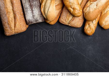 Assortment Of Fresh Bread On Black Background. Top View, Flat Lay, For Text. Concept Of Homemade Bre