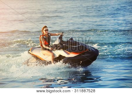 Young Adult Sporty Caucasian Woman Riding Jet Ski In Ocean Blue Water At Warm Evening Sunset. Beach