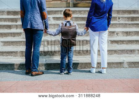 Parents And Pupil Of Primary School Stands Hand In Hand Before Stairs. Father, Mother And Son With B