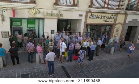 Alora, Spain - June 28, 2019: Large Crowd Outside Bank On Pension Day In Andalusian Village