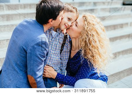 Parents Preparing To Send Her Child Back To School At Stairs In Morning. Mom Dad Kissing And Say Goo