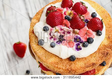 Victoria Sponge Cake With Whipped Cream, Sugared Flowers, Strawberries And Blueberries Over A White
