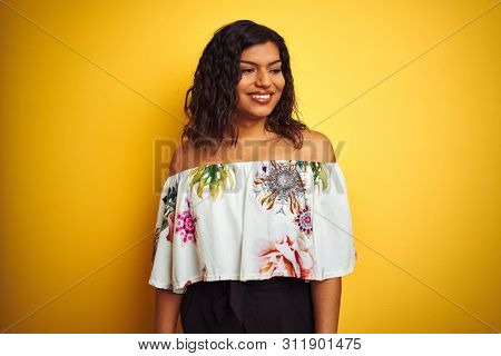 Transsexual transgender woman wearing summer t-shirt over isolated yellow background looking away to side with smile on face, natural expression. Laughing confident.